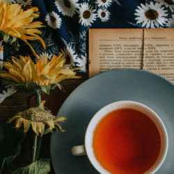 Community Abend, gelbe Blumen und eine Teetasse auf blumigem Tuch
